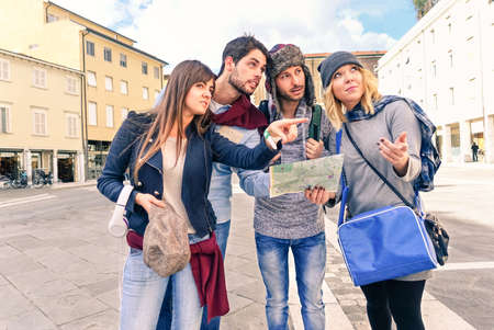 Group of tourists looking map - Couples of best friends in holiday lost in old town center -  Young students seek information on road map in city square - Concept of friendship tourism and education Stockfoto