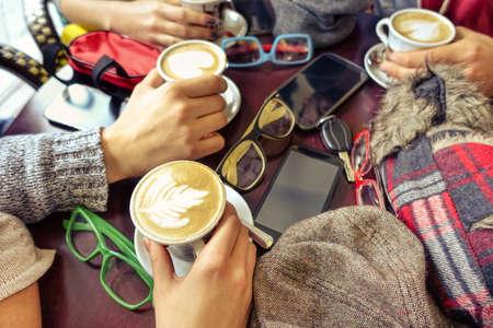 Handen die capuccino cup - Groep vrienden plezier in cafe drinken versierd melk en koffiemok - Begrip van vriendelijke zakelijke bijeenkomst met trendy drankjes en mobiele telefoon focus op de laagste cup Stockfoto