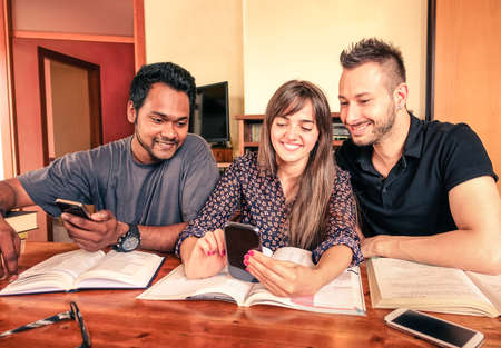 Multiracial students having fun with smartphone indoor - Best university friends reading books and looking cellphone inside house - Cheerful smiling young people are studying together - Vintage filter Stockfoto