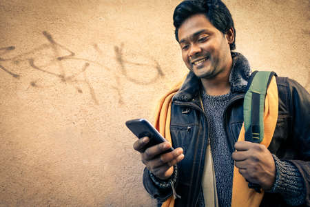 indian business man: Young indian man holding mobile phone - Cheerful asian model next to old urban wall - Soft vintage filtered look focus on person face