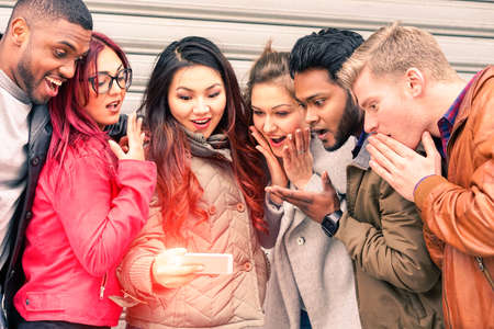 젊은 친구의 Multiracial 그룹 얼굴을 찾고 휴대 전화 새로운 기적 기술 - 혼합 된 인종 최고의 우정과 놀된 표정 개념 - 주요 초점 오른쪽 인도 남자 스톡 콘텐츠