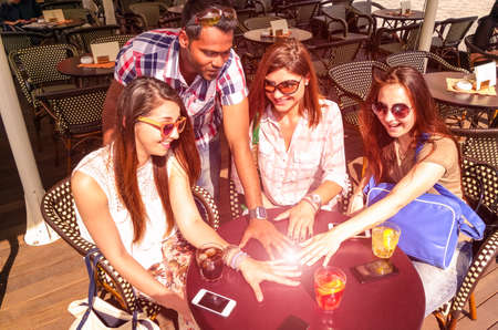 circle of friends: Multiracial group of friends hands circle on table with phones and drinks - Sun glow ball on hands as concept of friendship power between different cultures peoples - Main focus girl on the middle