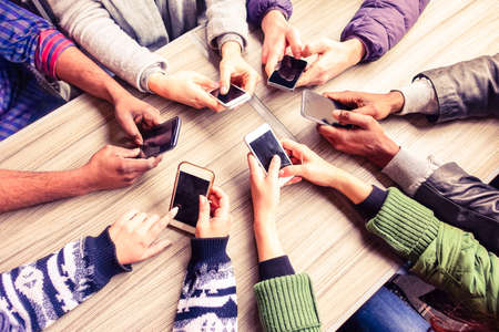 friends fun: Top view hands circle using phone in cafe - Multiracial friends mobile addicted interior scene from above - Wifi Connected people in bar table meeting - Concept of teamwork main focus on left phones Stock Photo