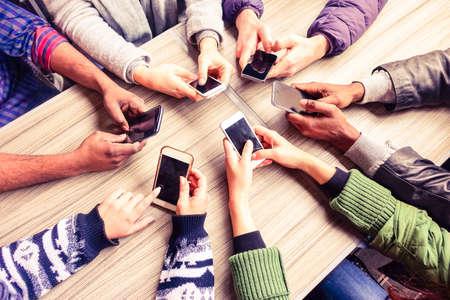 circulo de personas: Vista superior de las manos c�rculo que usa el tel�fono en caf� - Amigos multirraciales m�vil entre adictos escena desde arriba - Wifi Conectado personas en reuni�n mesa de bar - concepto de trabajo en equipo foco principal en los tel�fonos izquierda Foto de archivo