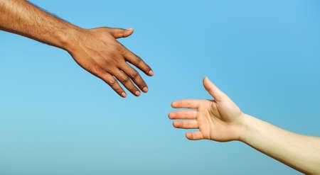 블랙 손 남자 돕는 흰색 사람 - 다른 문화와 종교 사이의 인도적 지원의 개념 - - 인종주의와 인종 문제에 대한 미국 다른 피부색 손 사람들 사이의 우정 스톡 콘텐츠