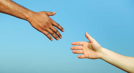 hands solution: Black hand man helping white person - Different skin color hands united against racism and racial problem - Concept of humane aid between different cultures and religion - friendship between peoples