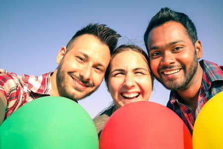 enjoing: Friends holding colorful balloons enjoing taking a selfie
