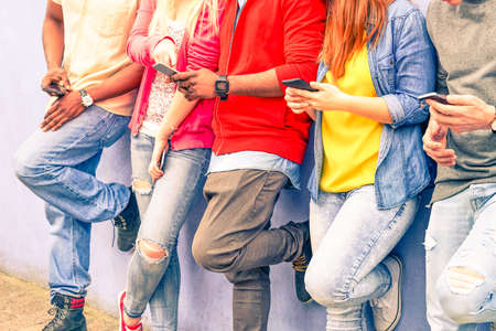 Multiracial group of friends texting sms and looking down to cell phone - Interracial students hands using mobile - Concept of young people addiction to web technology - Focus on hand of red hair girl Фото со стока