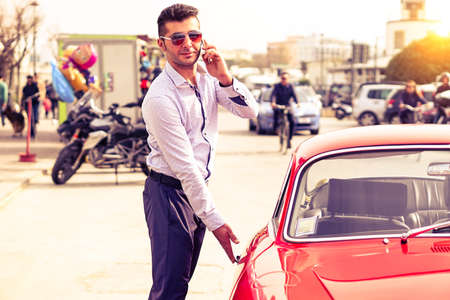 gigolo: Young handsome man with phone opening red car door - Attractive businessman talking at phone is getting into sport vehicle - Successful male person using mobile technology outdoors - Lifestyle concept
