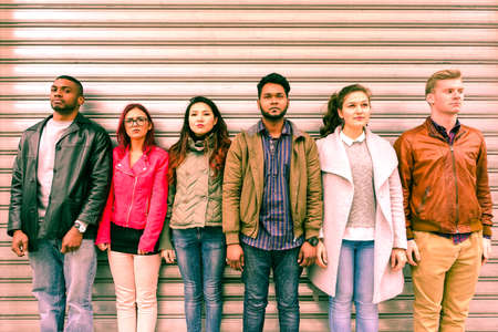수배 등 다민족 심각한 사람들 라인업 금속 압연 셔터 옆에 서있다 - 미래에 대한 차별과 청소년 문제의 개념 - 실업자 멀티 민족 친구들이 야외 줄 스톡 콘텐츠