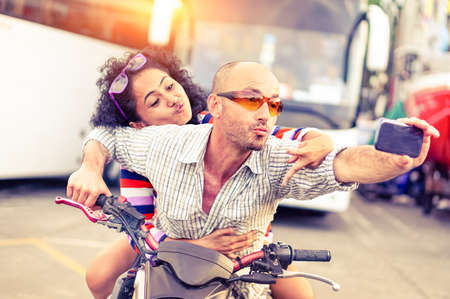 Couple of bikers taking selfie riding motorbike on urban road at sunset - Cool man and beautiful girl on sport motorcycle with funny facial expression - Concept of dangerous drive - Focus on male