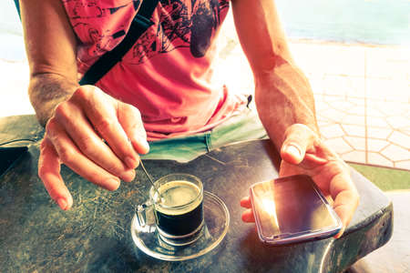 stiring: Man stirring coffee and holding smart phone at beach bar cafe restaurant - Hands with coffe cup and mobile top view on wooden table - Concept of relaxation humane habits and new technology addiction Stock Photo