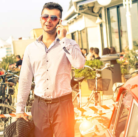 the next life: Handsome man talking on mobile phone - Fashion male model walking on street next to sport car - Concept of self confidence and successful life style - Sun halo and soft vintage filter look