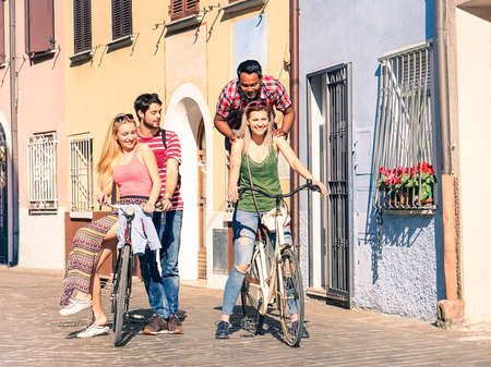 Multiracial group of young friends having fun riding bike in old city center - Mixed race couples with old bicycle in joyful moment during summer holiday - Cheerful teenagers playing on vintage cycle