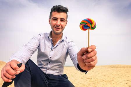 Junger Mann Entführer mit bösen Gesicht Kinder auf einsamen Strand bietet Lollipop - Gut aussehend Eltern Lollies zu kleines Kind zu geben - Konzept der Pädophilie und Entführung Gefahr für Kinder allein gelassen