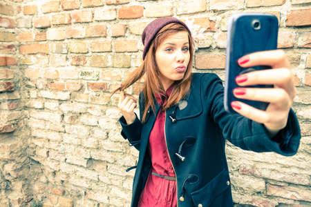 Mujer bonita joven que toma autofoto al aire libre - retrato de la moda femenina del invierno - Estudiante del adolescente que sostiene el teléfono móvil para la foto selfi junto al fondo de la pared de ladrillo - aspecto suave y brumoso de la vendimia filtrada