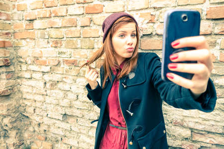 take a smile: Young pretty woman taking selfie outdoors - Female winter fashion portrait - Teenager student holding mobile phone for selfi photo next to brick wall background - Soft and hazy vintage filtered look