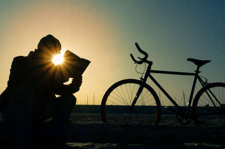 person reading: Man with bike silhouette - Senior reading on the beach at sunset - Hipster guy with bycicle sitting on the shore holding book background blue sky and sun light - Concept of leisure culture and health Stock Photo