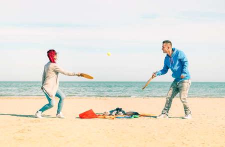 Couple jouant beach tennis jeu sur le sable avec l'océan bleu et fond de ciel - jeunes amis espiègles amusant avec des loisirs sains sur les vacances d'été - Notion de moment de joie et de vie active Banque d'images - 56299825