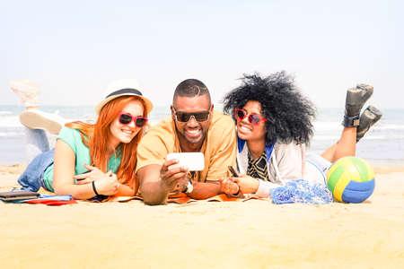 Multiracial friends having fun taking selfie lying on the beach Banco de Imagens