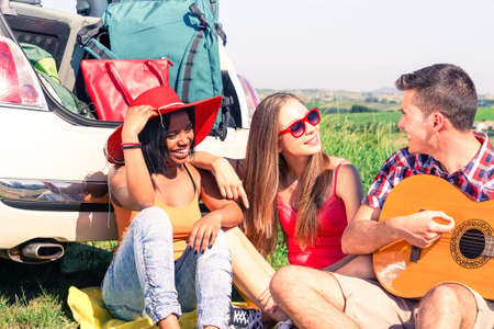 Multiethnic friends playing guitar sitting behind car on road trip - Multicultural teenagers having fun listening guitarist during spring break holiday - Concept of country style vacation and freedom