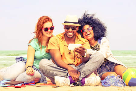 Multiracial friends having fun watching travel video at the beach - Happy group of students using mobile phone by the ocean - Concept of friendship and new technologies - Nostalgic vintage filter look Stockfoto
