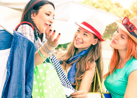 happy moment: Travel girlfriends at flea market fun and shopping moment - Young happy girls checking shirts size at street shop on summer vacation day - Cheerful women talking together - Focus on middle female