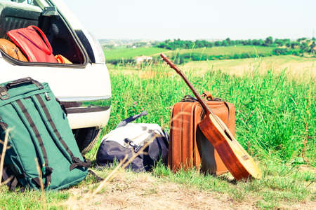 Travel suitcases guitar and backpack on countryside landscape background - Alternative summer holiday at national park - Road trip and freedom concept - Main focus on brown suitcase vintage filter