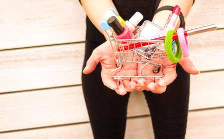 consumer products: Young woman holding little trolley with makeup inside of it Stock Photo