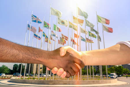 political and social issues: Multiracial handshake with world flags background - Black and white men hand shake team against racism - Governance leaders agree solution to actual refugees political events concept - Focus dark hand Stock Photo