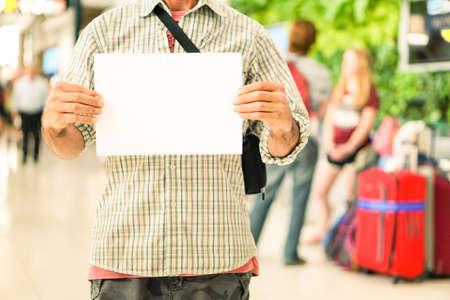 letreros: El hombre da sostener el letrero vacío en el punto de encuentro aeropuerto internacional - ocasionales chico joven con la muestra en blanco para el texto de publicidad está recibiendo los viajeros en la puerta de llegada - Foco principal en manos de los hombres Foto de archivo