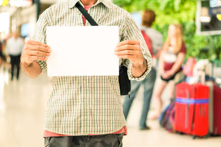 Man hands holding empty signboard at international airport meeting point - Young casual guy with blank sign for advertising text is receiving travelers at arrival  gate -  Main focus on male hands Stockfoto