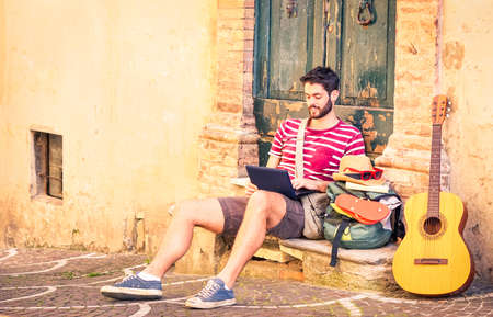 Handsome travel man using pc sitting in front of old house - Music artist relaxing at city alley - Concept of freedom and summer world tour backpacker style - Nostalgic vintage filter with vignetting