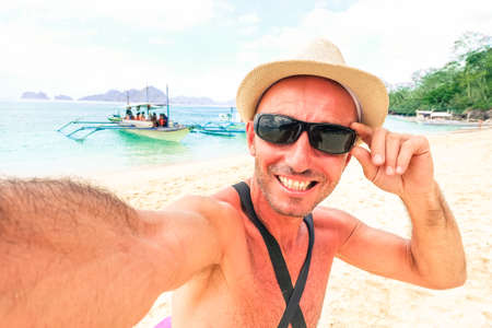 happy moment: Travel man taking selfie on tropical beach at Palawan in Philippines Islands - Male funny self photo on blue lagoon tourist tour - Concept of happy moment in paradise destination around world