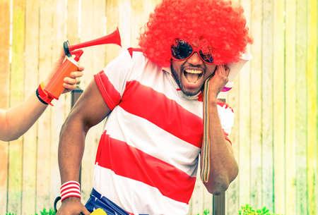 サッカーのアフロ ・ アメリカ人ファンは面白いかつらとアフリカ黒人の男性が不快なノイズ - 健康危険性の概念によってろう者叫んでいる国際的な