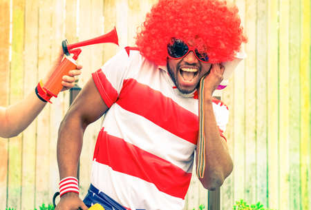 unpleasant: Afro american man fan of football have fun with bizarre look for international sport event - Black african male with funny wig is screaming deafened by unpleasant noise - Concept of health danger