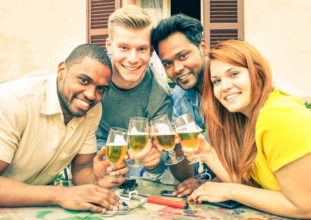 prosit: Multiracial friends beer cheers for school ending - Cheerful multiethnic teens holding drink glasses at street old city bar - Concept of fun and friendship in group of different races young people Stock Photo