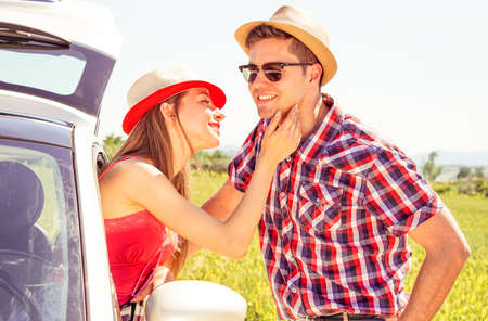 romantic man: Couple love moment at summertime road trip - Young woman caress boyfriend face from  car window on countryside background - Summer travel concept with models in romantic love and tenderness posing
