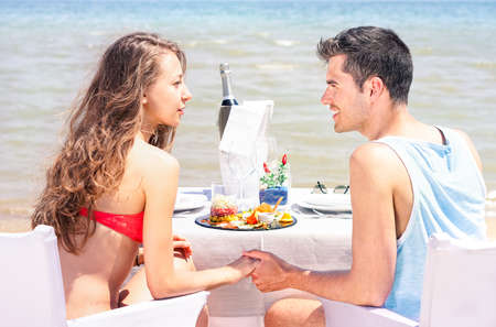 joys: Young couple eating at beach restaurant with blue ocean view - Teenagers romantic  lunch time moment on resort terrace with sea background - Summer concept of love and life joys - Sunny day lights