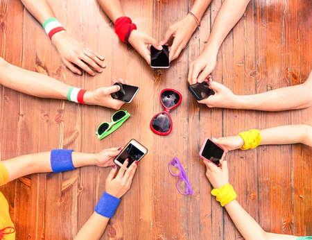 왼쪽 아래 전화에 초점 - 개념 일상 생활에서 현대 기술 중독 - 새로운 모바일 들고 국제 사람들을 나무 테이블 주위에 - 위의 전화 뷰를 사용하여 많은