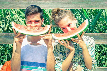 Positive couple eating watermelon at countryside picnic - Young friends having fun outdoor playing funny faces with seasonal red fruit - Concept of joyful moment on summertime - Vintage filter look