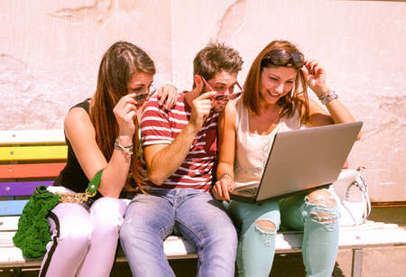 web surfing: Students with laptop looking surprised by results of examinations - Three cheerful young best friends sharing news and web surfing - Modern concept of youth and communication - Marsala filter look Stock Photo