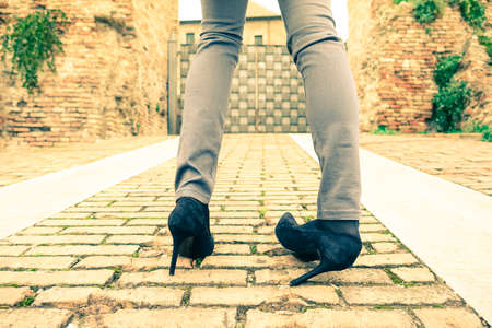 Woman walking on high heeled shoes - Closeup of young girl legs with twisted ankle - Slim teenager wearing trendy tight jeans pants - Concept of youth fashion and social problems related to anorexia