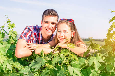 biological vineyard: Young positive couple overlooking vine leaves in sunny summer day - Agricultural entrepreneurs leaning on grape variety smiling and looking at camera - Concept of success positivity and team work