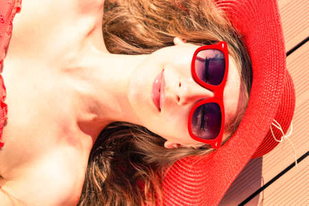 sun tanning: Glamorous young woman sun tanning at pool deck  - Beautiful girl sunbathing close-up of face view from above  - Concept of beauty and skin care to prevent sunburn during summer holiday