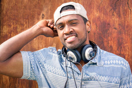 self confident: Young afro american man smiling at camera - Self confident black guy with cap staring into the eyes on wood background - Portrait of attractive african male wearing headphones