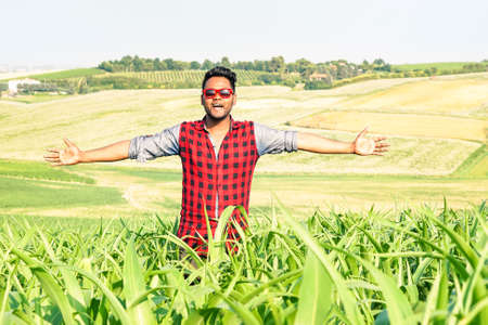 Young indian farmer with open arms in a corn field - Cheerful asian man walking through countryside with a freedom attitude and positive expression - Concept of life joyful moment and human happiness
