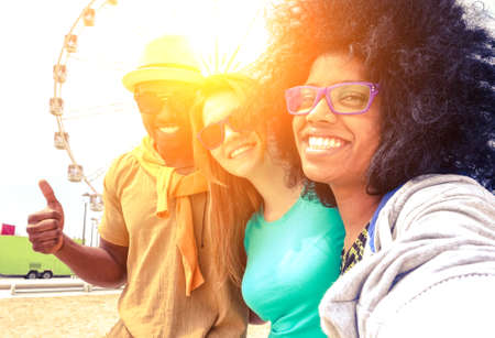 Afro hair girl taking selfie with best friends at ferris wheel at sunset - Happy multiracial group of students having fun with smartphone photo camera outside- Warm sun halo filter with vintage tones