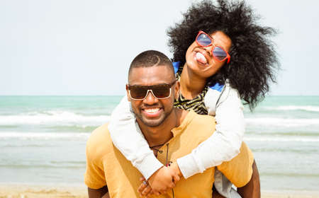 Young afro american couple playing piggyback ride on beach - Cheerful african friends having fun at day with blue ocean background - Concept of lovers happy moments on summer holiday - Vintage filter Stock Photo