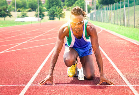 jamaican man: Afro american athlete ready to sprint at starting line - Runner kneeling on blocks of red athletics track - Concept of human concentration at sport competition - Soft vintage filter and sun reflection